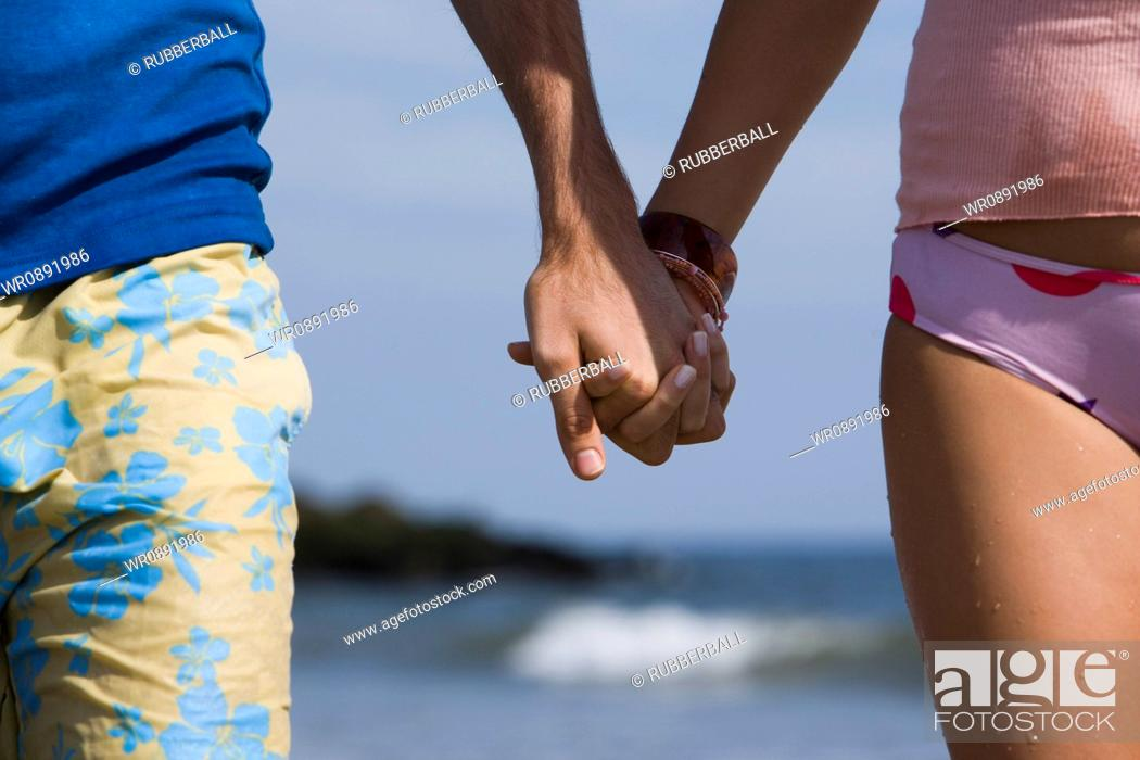 Stock Photo: Close-up of a young couple holding hands.