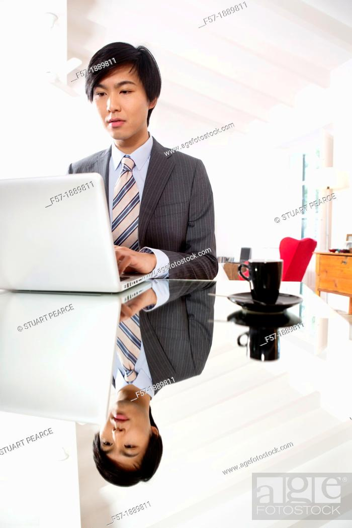Stock Photo: Young Asian man working on his laptop computer.