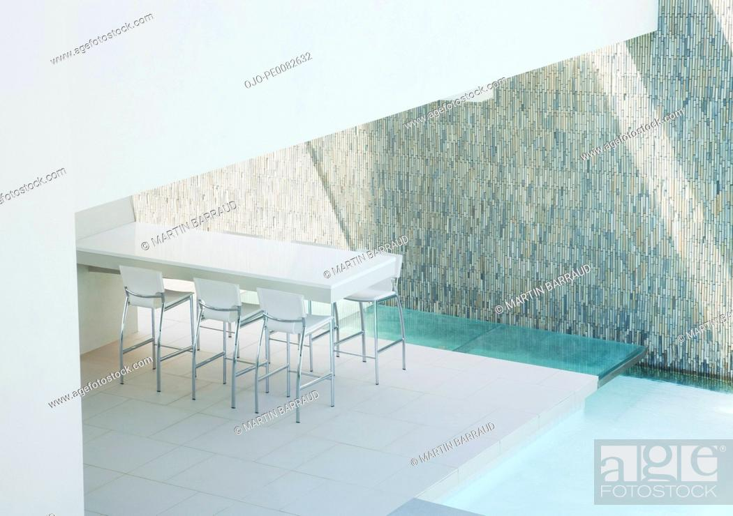 Stock Photo: View of barstools and counter on patio next to swimming pool.