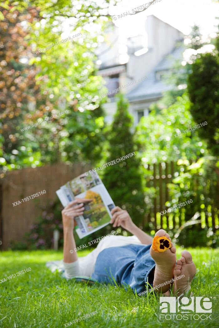 Imagen: Woman relaxing on grass and reading magazine.