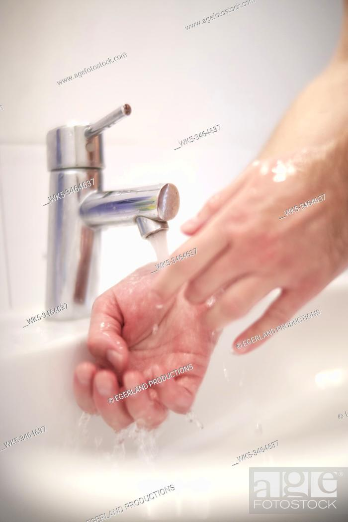 Stock Photo: Man washing his hands.