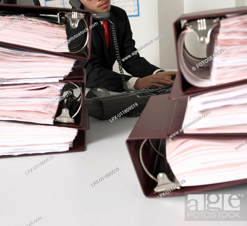Stock Photo: Office Worker Typing While on Phone.