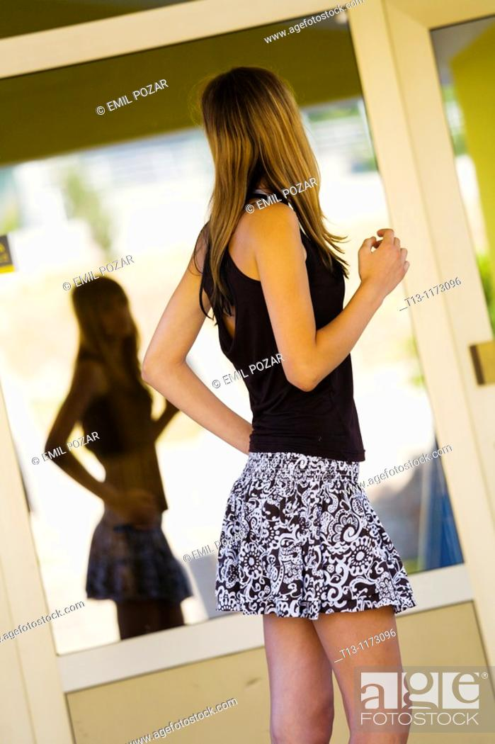 Stock Photo: Posing before a reflective window young teenager girl.