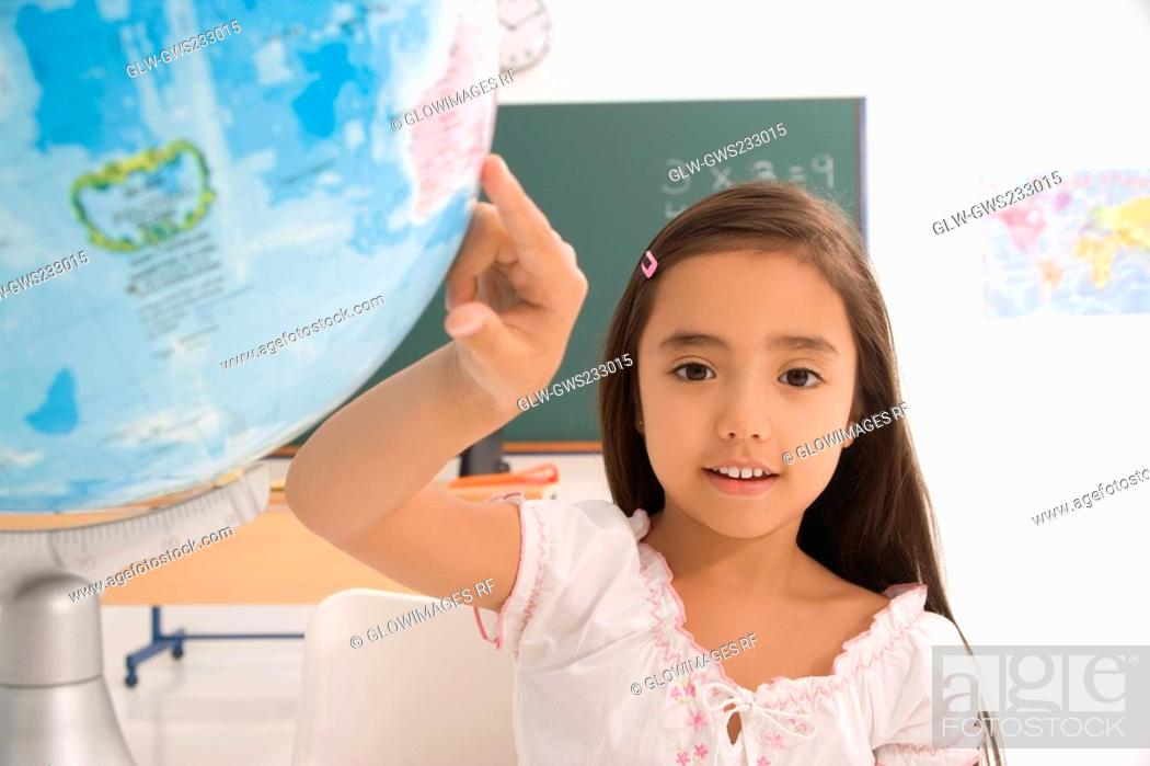 Stock Photo: Portrait of a schoolgirl pointing on a globe.