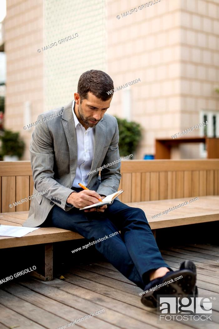 Stock Photo: Businessman sitting on a bench writing into diary.