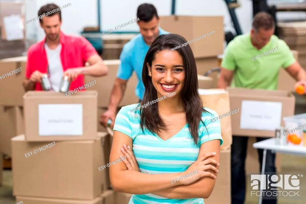Stock Photo: Portrait of a smiling volunteer with arms crossed.