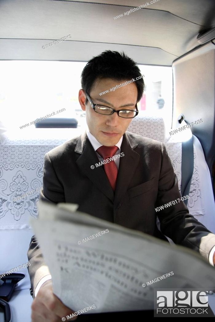 Stock Photo: Businessman reading newspaper in car, portrait.