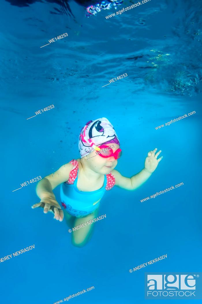 Stock Photo: 2 years girl in a swimming goggles learning to swim underwater in the pool, Odessa, Ukraine.