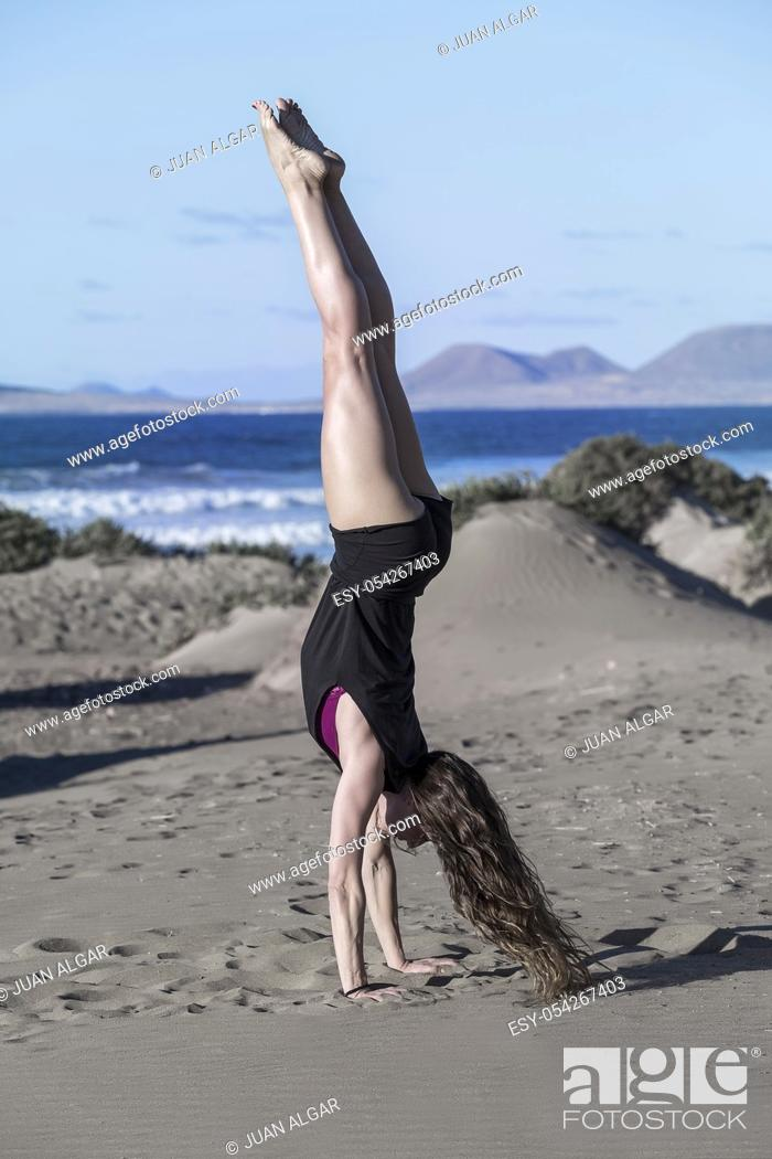 Stock Photo: Side view of brunette in black sportive shorts doing handstand on sandy beach balancing in sunlight.