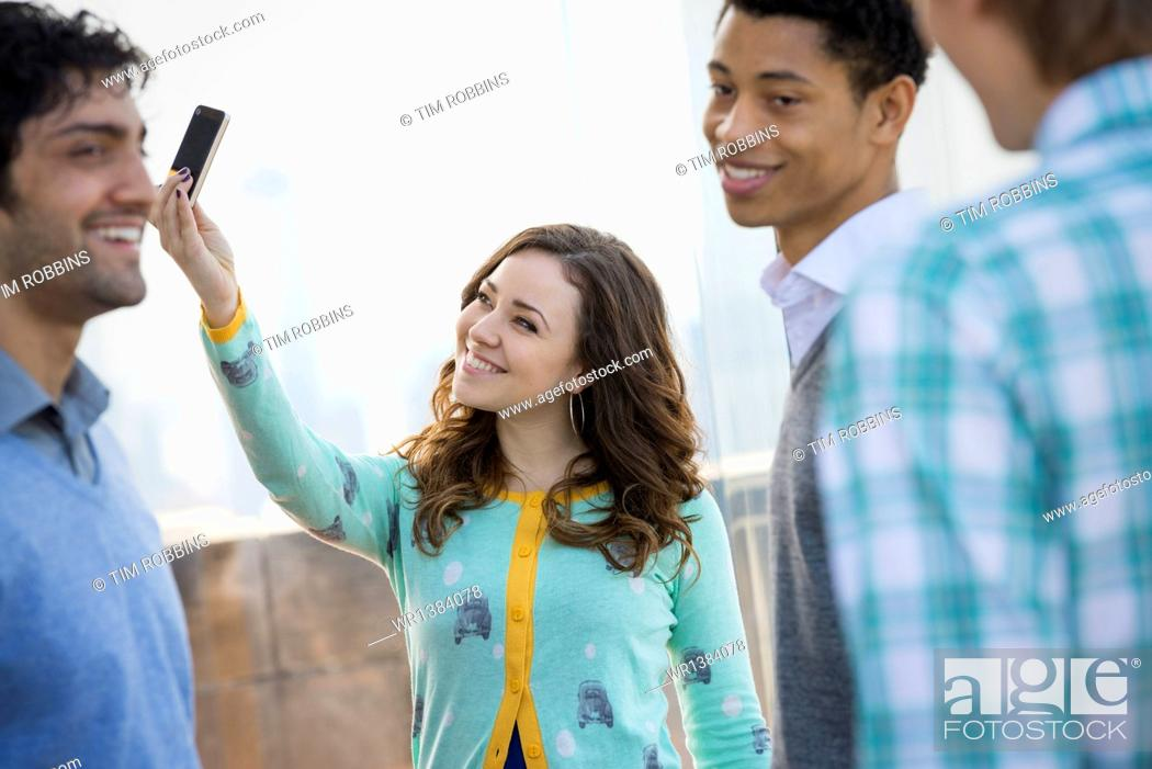 Stock Photo: New York City. An observation deck overlooking the Empire State Building. A woman using a smart phone to take an image. Three young men.