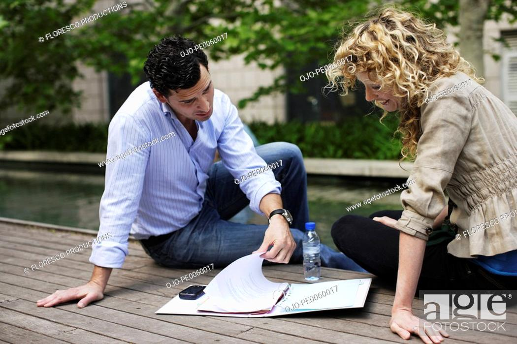 Stock Photo: Two businesspeople outdoors on deck with paperwork.