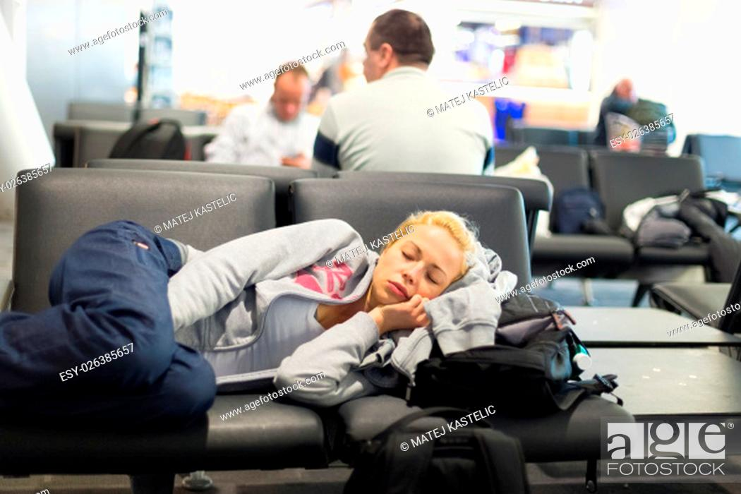 Stock Photo: Tired female traveler sleeping on the airpot departure gates bench with all her luggage by her side. Tireing travel concept.