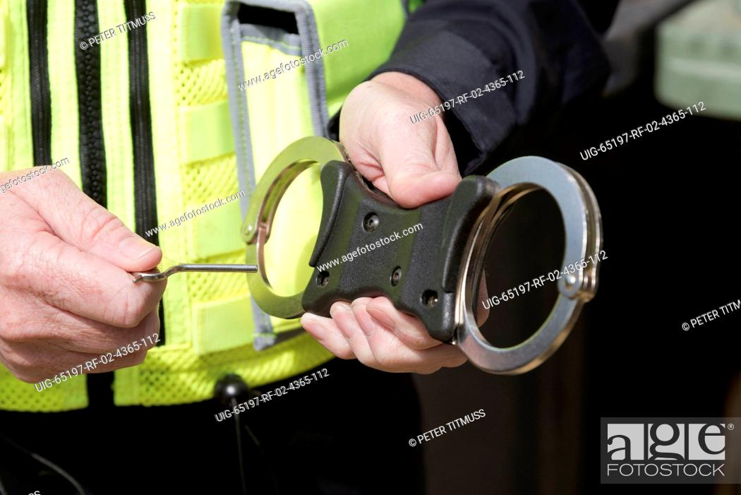 Photo de stock: Close up of police officer holding the key to a pair of handcuffs.