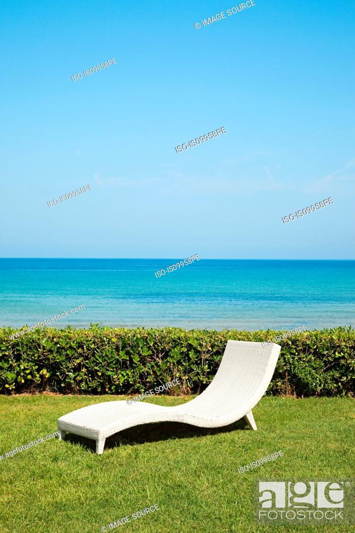Stock Photo: Empty white sun lounger on grass.