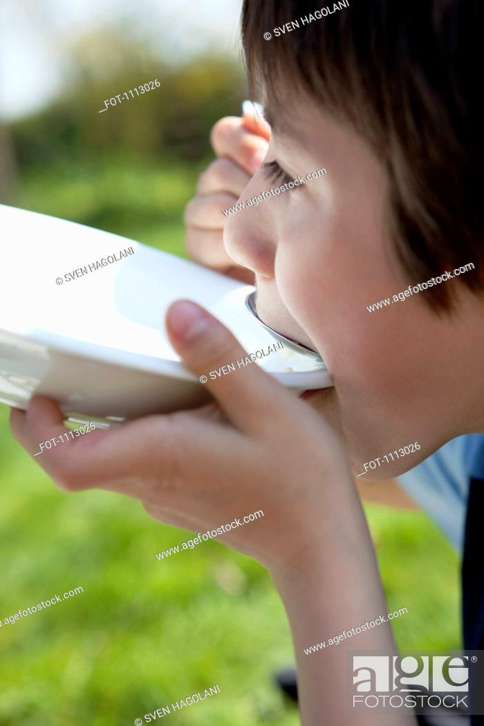 Stock Photo: A young boy eating out of a bowl with a spoon.