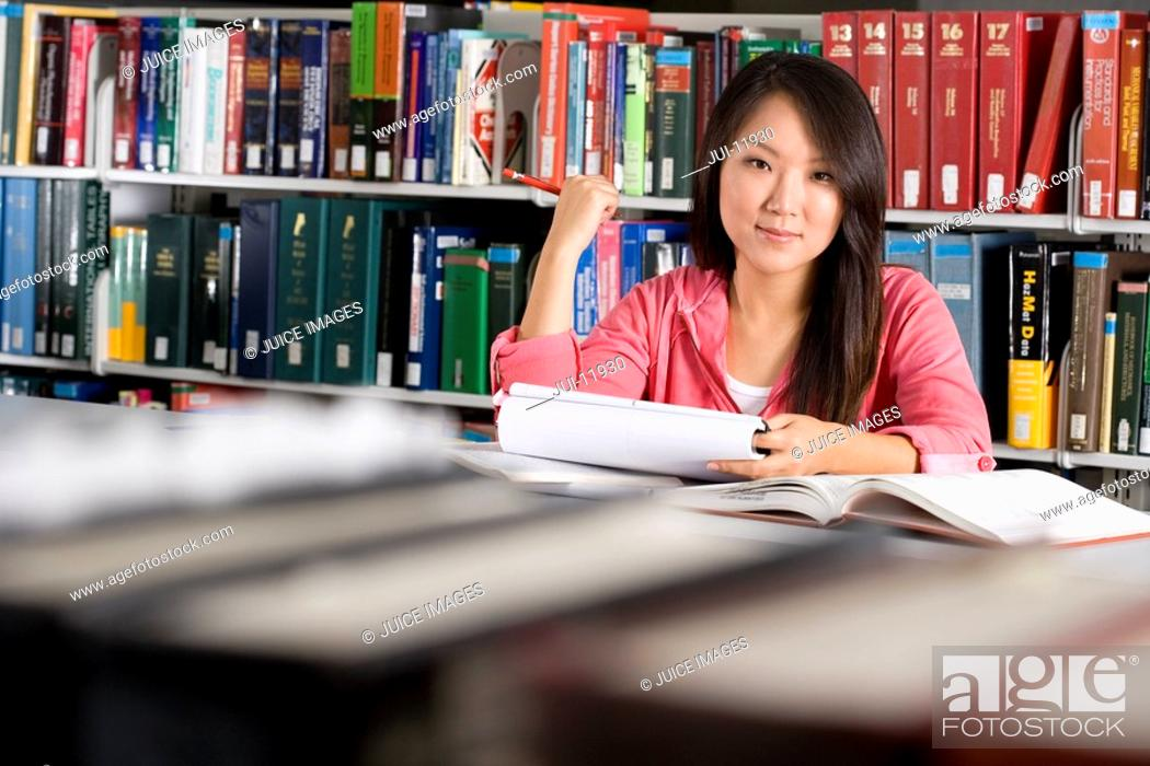 Stock Photo: Woman studying in library, smiling, portrait.