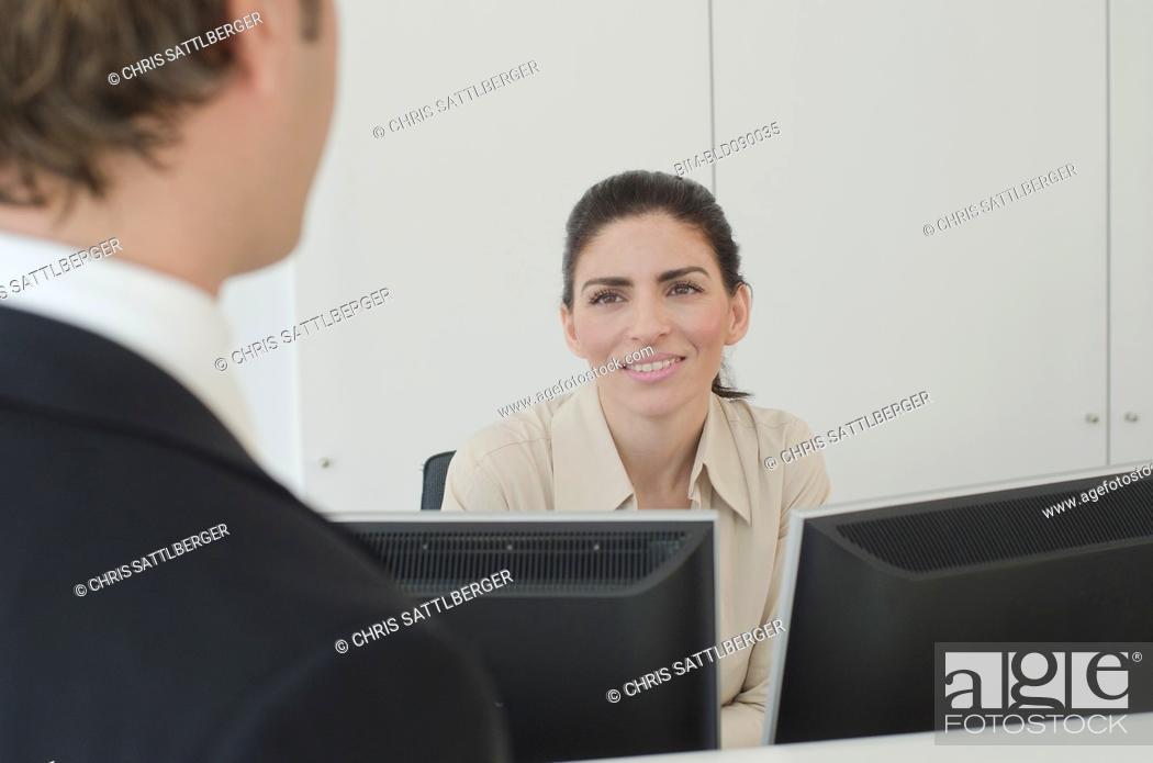 Imagen: Hispanic businessman talking to receptionist.