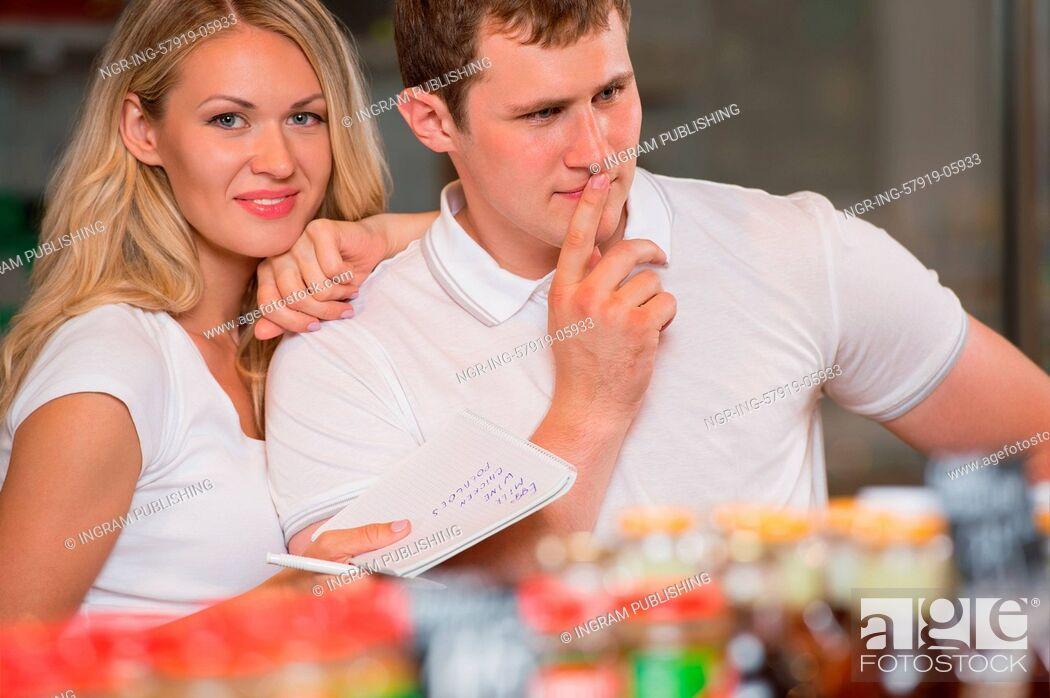 Stock Photo: Image of positive couple choosing products in supermarket with list of things to buy.