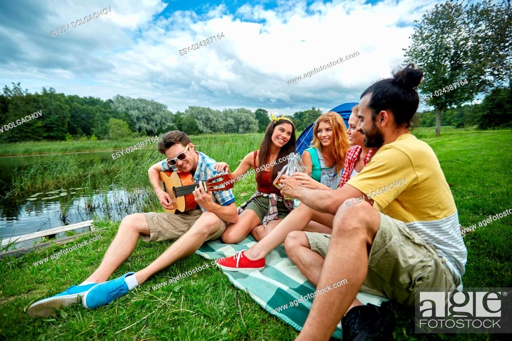 Stock Photo: travel, tourism, hike, picnic and people concept - group of happy friends with tent and drinks playing guitar at camping.