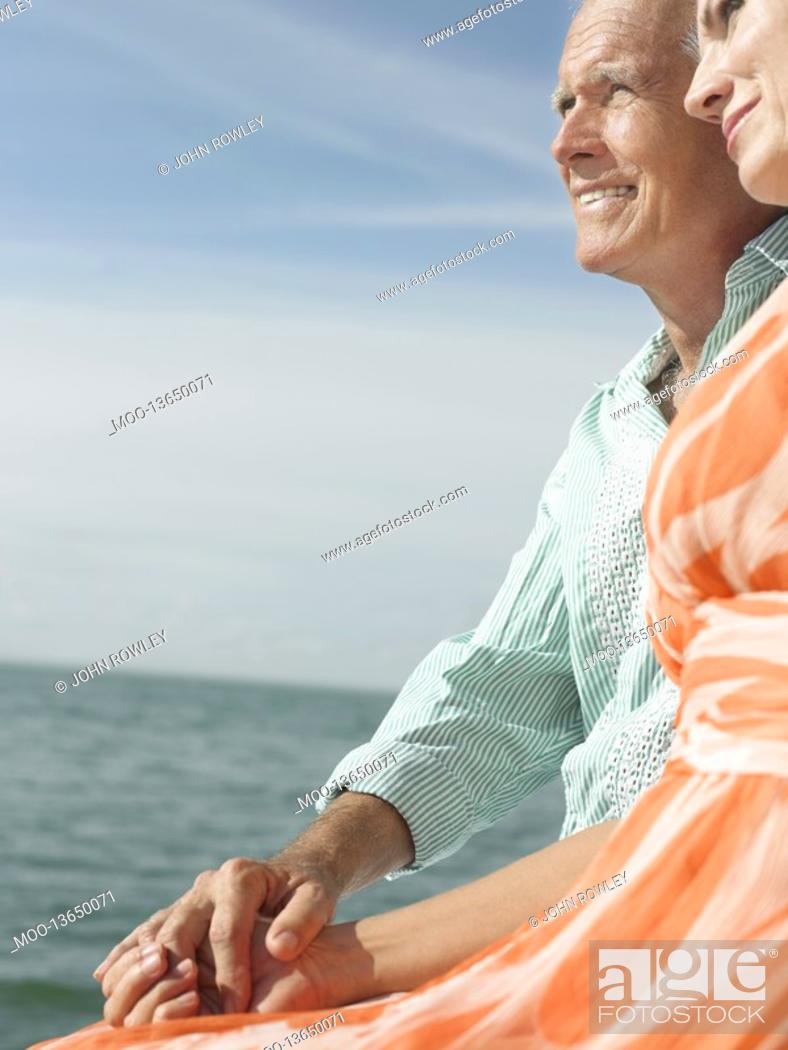Stock Photo: Couple sitting on edge of pier looking at view side view.