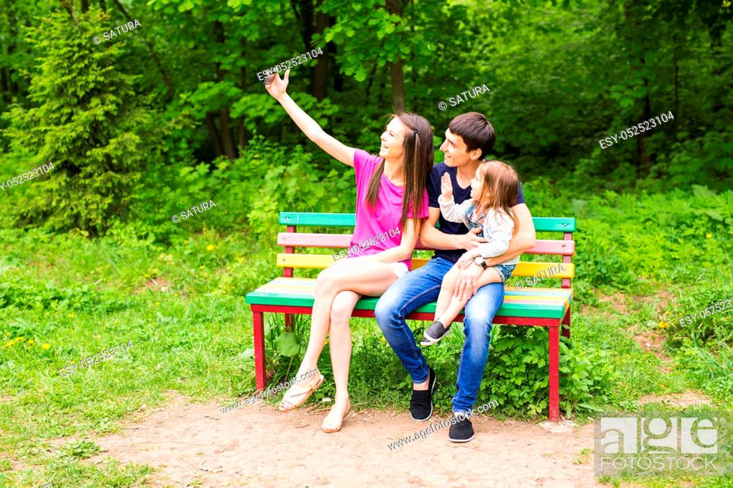 Stock Photo: Happy family in the park taking selfie on a sunny day.