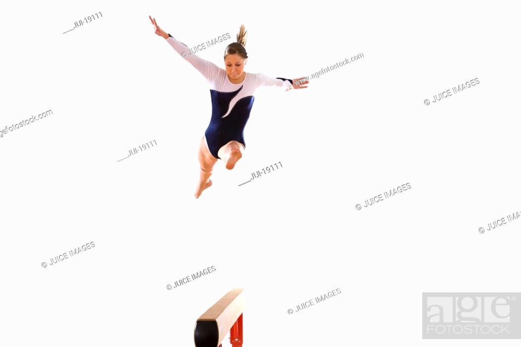 Stock Photo: Female gymnast performing jump on balance beam, low angle view.