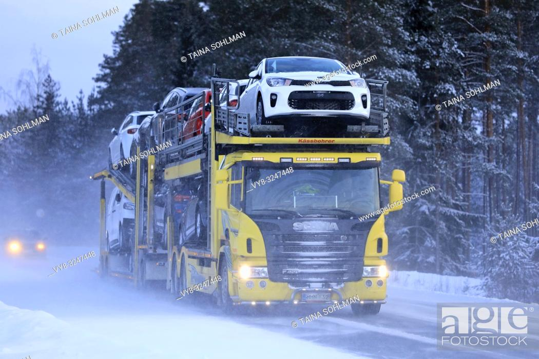 Imagen: Salo, Finland - January 18, 2019: Yellow Scania car carrier truck travels in the snow trail of another vehicle on a day of winter snowfall in Finland.