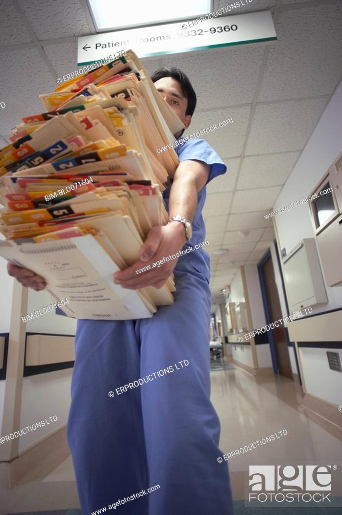 Stock Photo: Hispanic male doctor carrying charts.