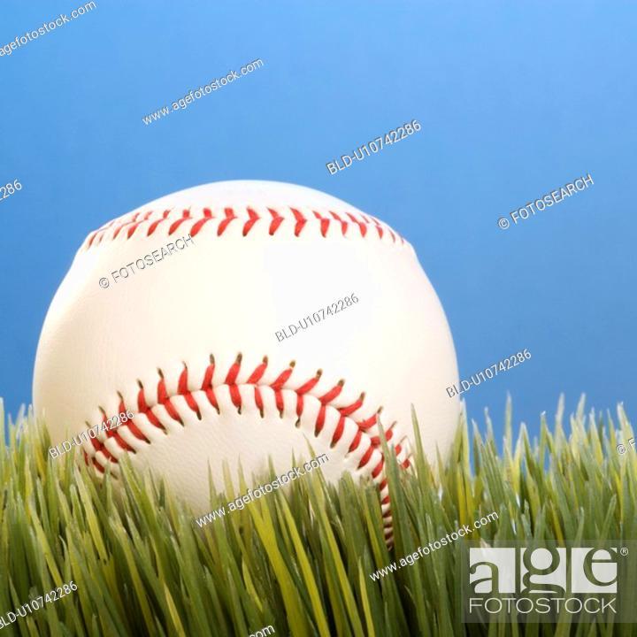 Stock Photo: Studio shot of a baseball resting in grass.