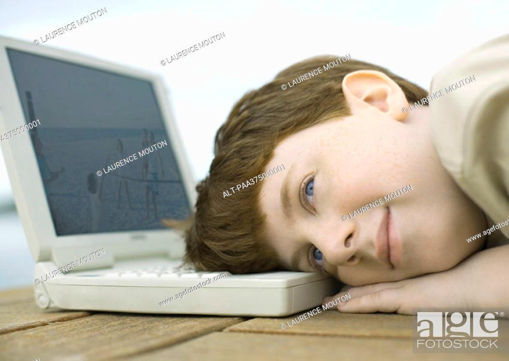 Stock Photo: Boy resting head on laptop.