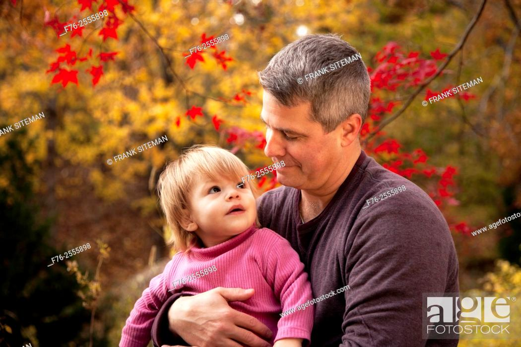 Stock Photo: Father, in his 30s, holding his one year old daughter and holding her gaze with a loving look while sitting in their backyard in the fall with red maple leaves.