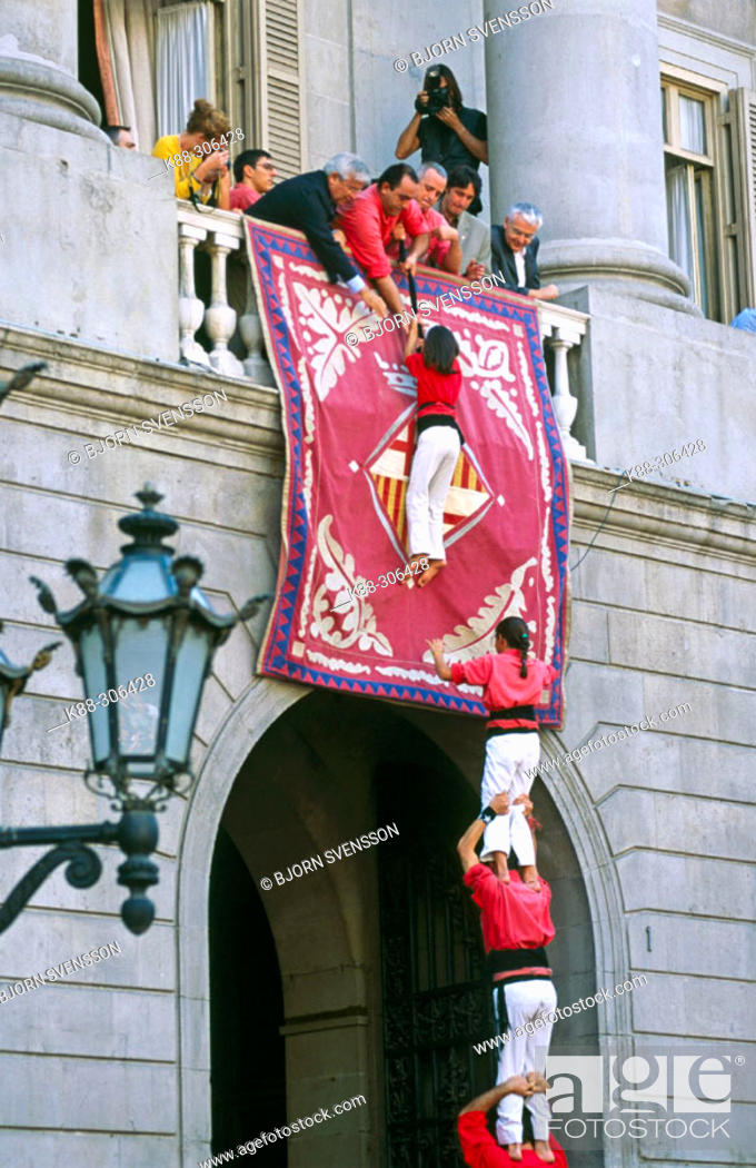 Stock Photo: A young 'Castellera' (member of a human tower) climbs up to the mayor of Barcelona, who is on the City Hall balcony. Plaça de Sant Jaume. Barcelona.
