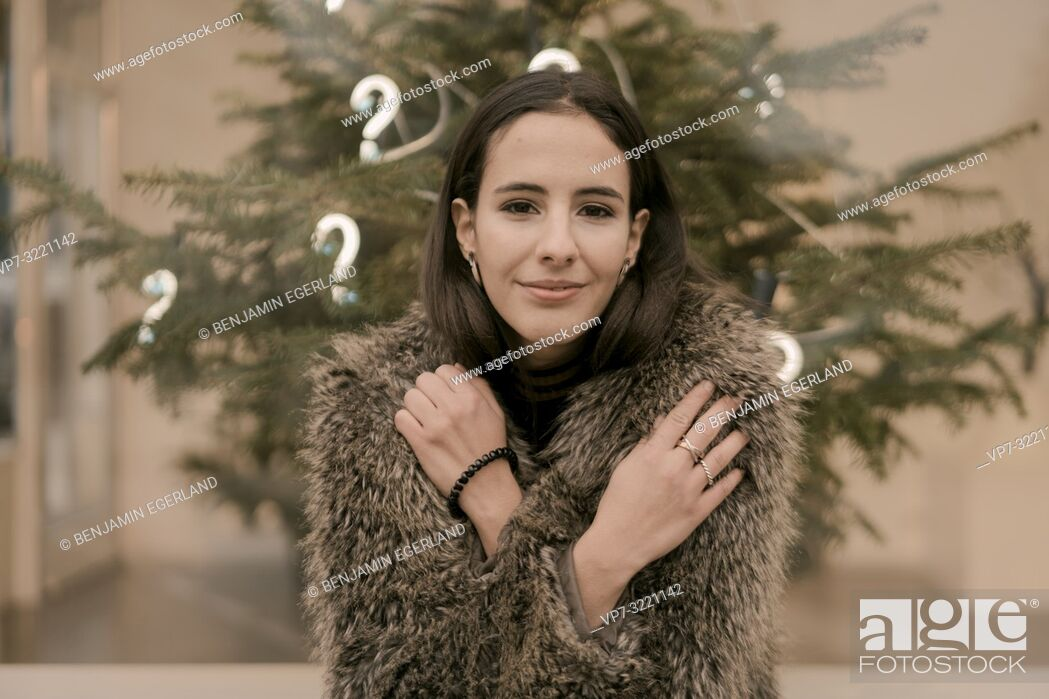 Stock Photo: content woman in front Christmas tree with lights of question marks, in Munich, Germany.