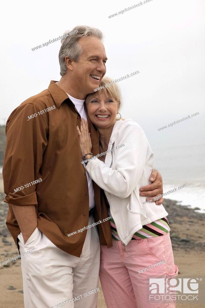 Stock Photo: Mature couple embracing on beach.
