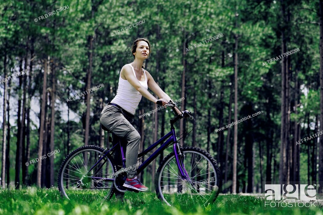 Stock Photo: Woman sitting on bicycle in forest.