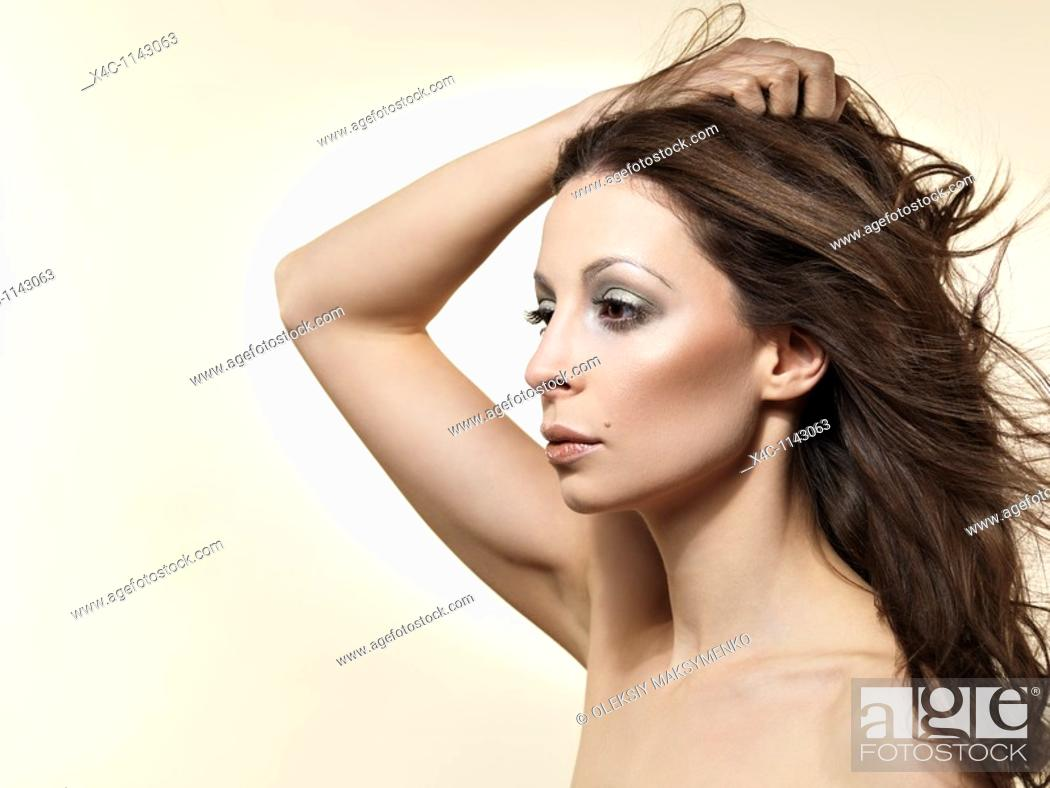 Stock Photo: Beautiful young woman portrait isolated on beige background.