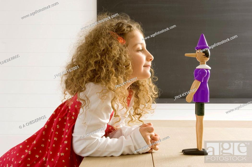 Stock Photo: Side profile of a girl playing with a toy.