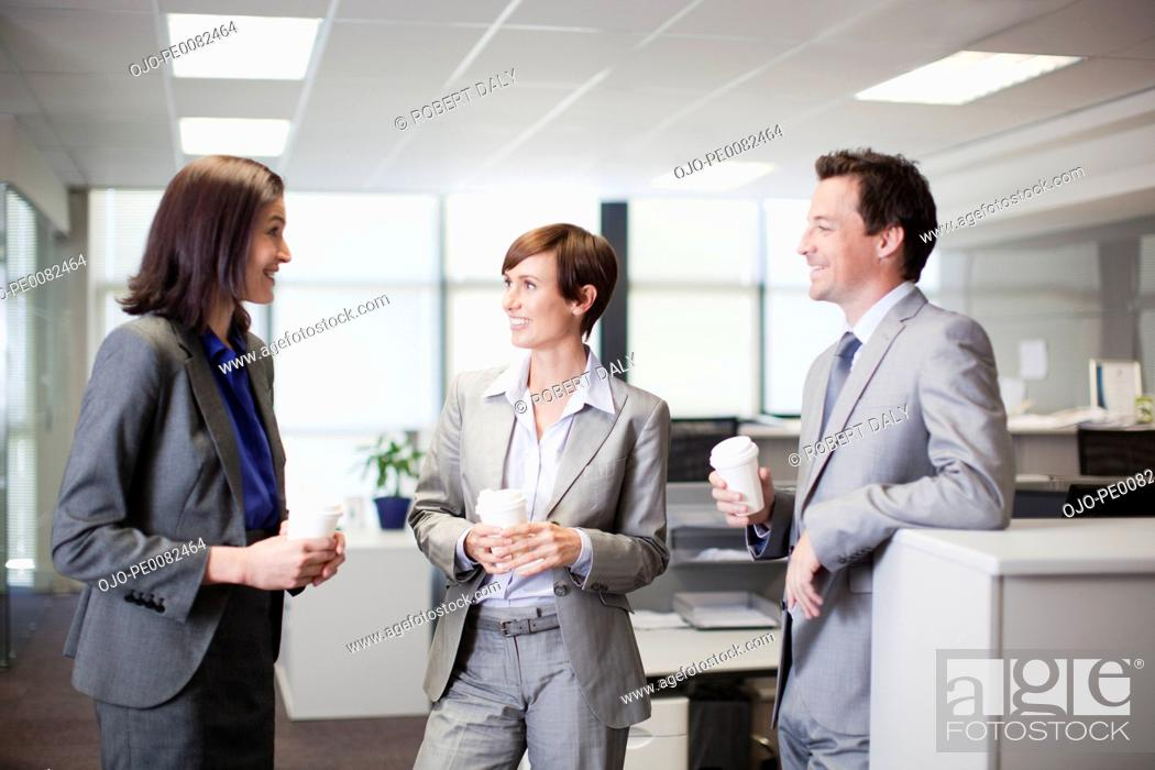 Stock Photo: Business people drinking coffee and talking in office.