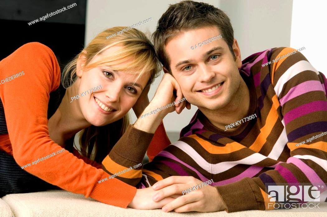 Stock Photo: Portrait of a young couple lying on a couch and smiling.