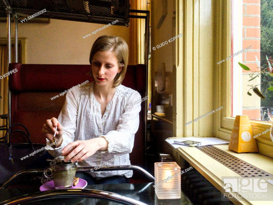 Stock Photo: Tilburg, Netherlands. Caucasian female preparing her cup of tea while visiting a cafe for a meeting.