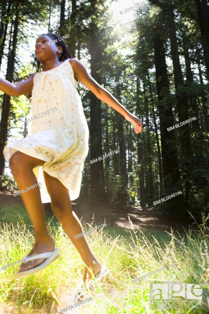 Stock Photo: African girl running in woods.
