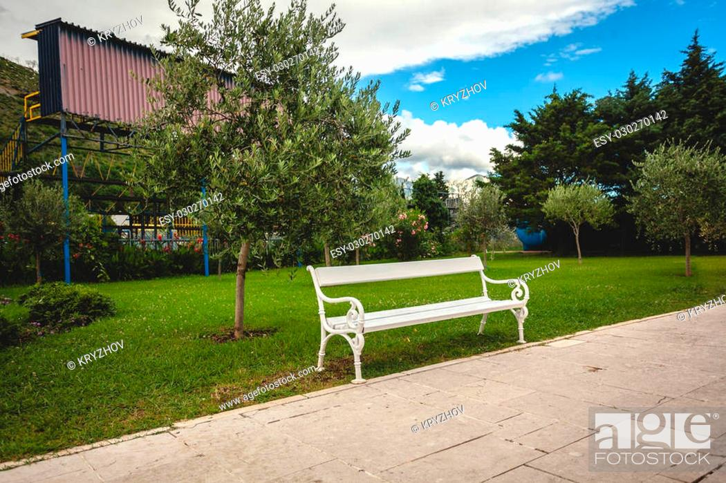 Stock Photo: Beautiful view of white bench in park with trees and lawn.
