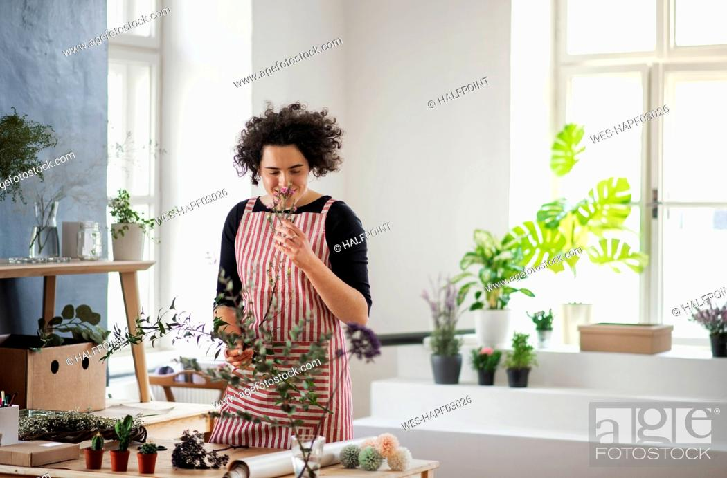 Stock Photo: Smiling young woman smelling at plant in a small shop.