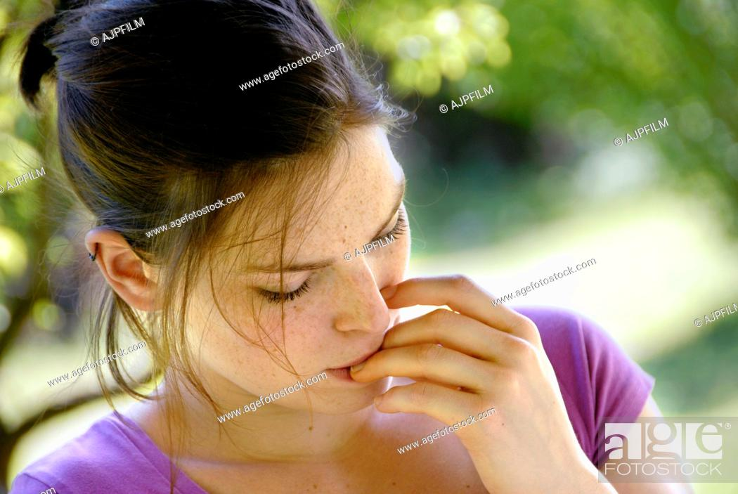 Stock Photo: 20 years old woman in a garden biting her finger nails.