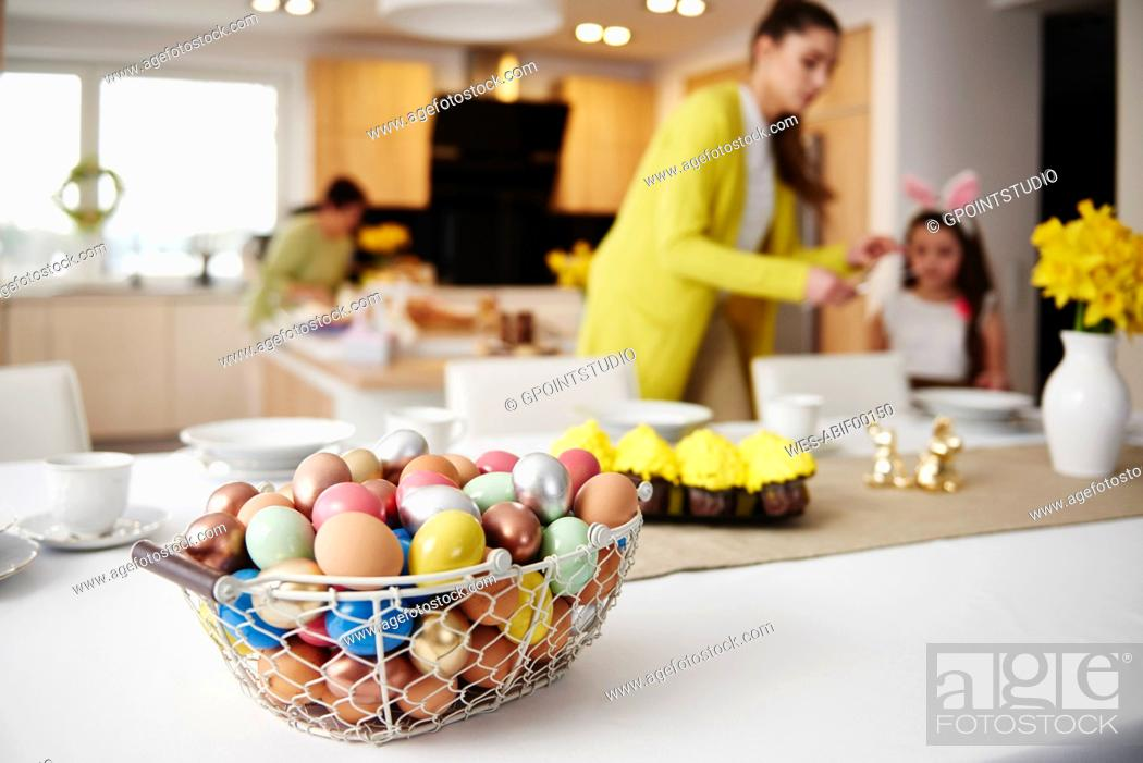 Stock Photo: Easter eggs in basket on table at home with mother and daughter in background.