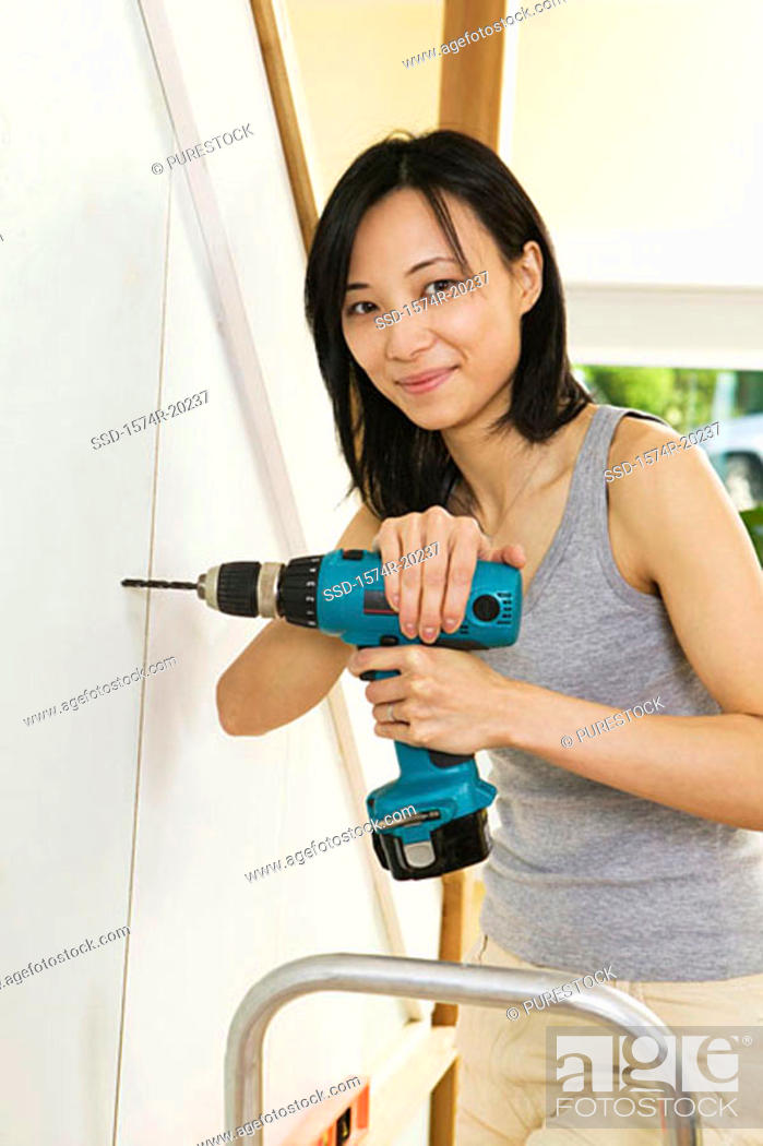 Stock Photo: Portrait of a young woman drilling into a wall.