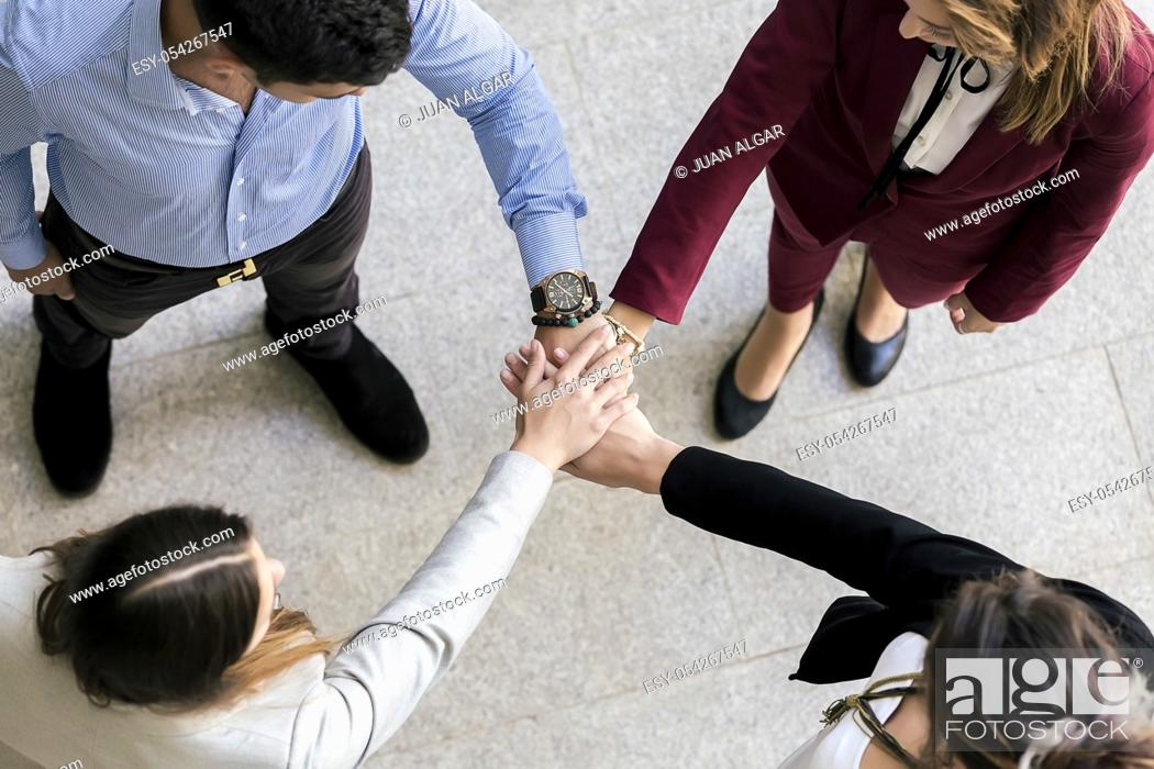 Stock Photo: From above people joining hands during the team building in the coworking space. Horizontal indoors shot.