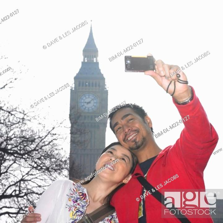 Stock Photo: Asian couple talking own photograph with clock tower in London.