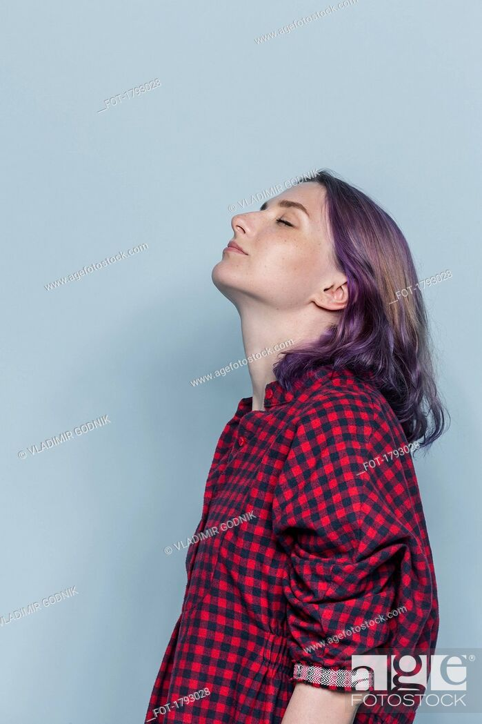 Stock Photo: Side portrait of young woman with dyed hair and eyes closed against gray background.