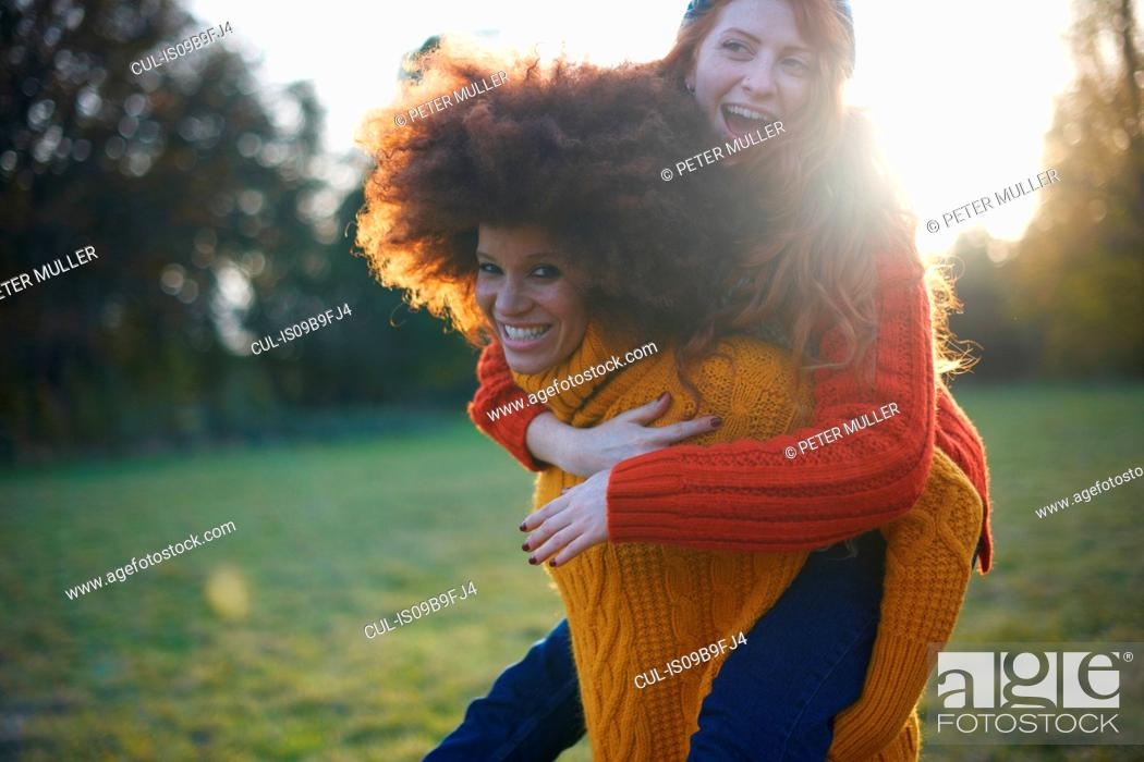 Stock Photo: Two young women, in rural setting, young woman giving friend piggyback ride.